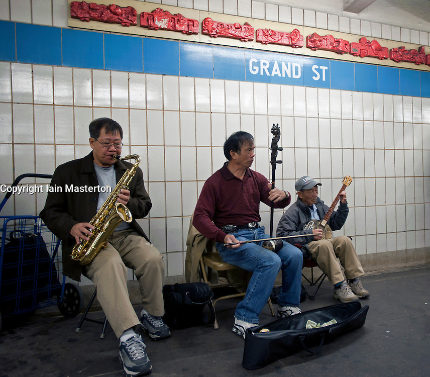 Chinese senior men playing traditional musical instruments at Grand Street subway station in Chinatown New York City USA