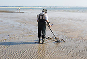 Male detectorist using metal detector at low tide, sandy beach Studland Bay, Swanage, Dorset, England, UK
