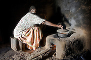 Madam Betty Okiru cooking in a hut using a fuel-efficient stove. The stove is constructed in a way that uses the least amount of wood, a chimney is built into the back to remove the smoke from the hut. She lives with her husband Francis Okiru in the Pallisa district of Uganda. Francis joined the Kulika project in 2003 and received sustainable organic agriculture training.