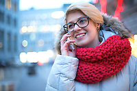 Happy woman using cell phone outdoors during winter