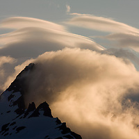 USA, Alaska, Katmai National Park, Windswept clouds above glacier-covered mountains along Hallo Bay at sunset on summer evening