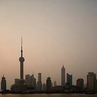 Asia, China, Shanghai, Silhouette of Oriental Pearl TV Tower and skyscrapers of Pudong skyline viewed through haze on summer morning.