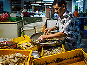 24 AUGUST 2018 - GEORGE TOWN, PENANG, MALAYSIA: A shrimp seller sorts shrimp imported from Thailand in Chowrasta Market in central George Town. Chowrasta Market was originally built in 1890 and is the older of two traditional markets in George Town. The original building was torn down and replaced with a modern building in 1961 and has been renovated several times since.     PHOTO BY JACK KURTZ