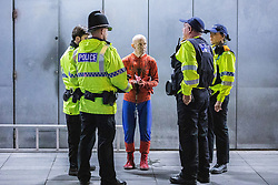 © Licensed to London News Pictures. 01/09/2019. Manchester, UK. Several dozen police intervene after Extinction Rebellion supporters climb on to the roof and drop a banner from cafes in Piccadilly Gardens as roads around Deansgate remain closed to traffic by environmental campaigners . One of the protesters, dressed as Spiderman , is understood to be Kevin Charles Godin-Prior . Manchester City Council has declared a climate emergency but activists say the council's development plans do not reflect this . Photo credit: Joel Goodman/LNP