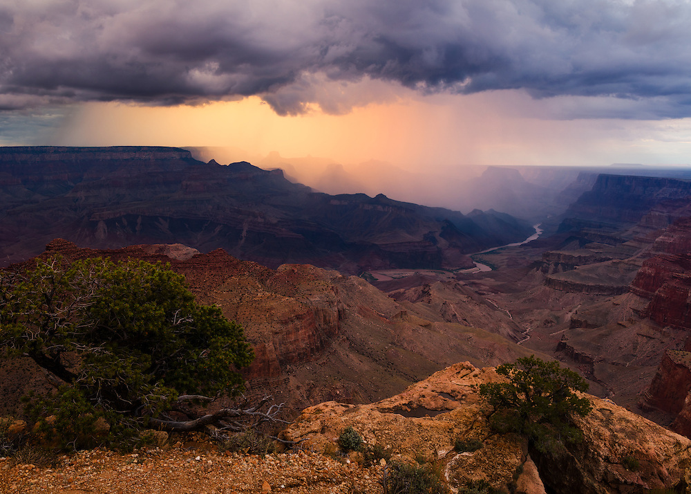 Rain falling from a monsoon thinderstorm is backlit by the setting sun. From Desert View at Grand Canyon National Park in Arizona.