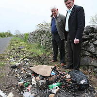Local Resident Des Lynch and Joe Cooney,O'Callaghans Mills with some of the rubbish left along the road at Clooney.<br /> <br /> Photograph by Eamon Ward