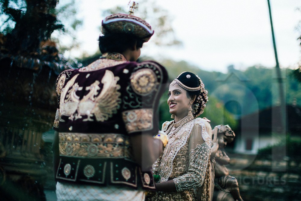 A Sri Lankan couple take wedding photos in traditional dress, early morning in downtown Kandy, Sri Lanka, Asia