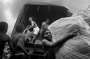 Displaced men unload a truck with mattresses, brought by the British NGO Oxfam, in the village of Pavarandó in the Urabá region. The village had become the site for a refugee camp as thousands of displaced Afro-Colombian families were halted here by the Colombian Army after being displaced from their homes in the Salaquí area of the Lower Atrato River region.