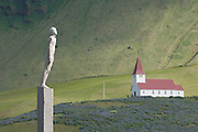 Statue of person, church in background. Vik. Iceland.