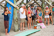 Charleston area surfers join the Mayor of Folly Beach Tim Goodwin (center left) gathered for a traditional memorial paddle out to honor and remember the nine people killed at the historic mother Emanuel African Methodist Episcopal Church June 27, 2015 in Folly Beach, South Carolina. Earlier in the week a white supremacist gunman killed 9 members at the historically black church.