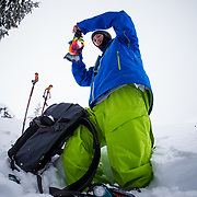 Tyler Hatcher cleans his goggles before another run in the Cascade backcountry.