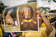 05 DECEMBER 2012 - BANGKOK, THAILAND: A woman holds up a picture of the King on the Royal Plaza Wednesday while she waits to see Bhumibol Adulyadej, the King of Thailand, before his public audience at the Mukkhadej balcony of the Ananta Samakhom Throne Hall. December 5 is a national holiday. It's also celebrated as Father's Day. Celebrations are being held across the country to mark the birthday of Bhumibol Adulyadej, the King of Thailand.    PHOTO BY JACK KURTZ