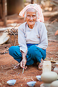 Old woman smoking at pottery in Mynamar