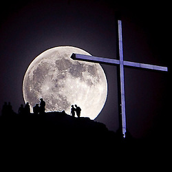 "A ""supermoon"" rises over Table Rock and lighted cross near Boise, Idaho. Saturday June 22, 2013"