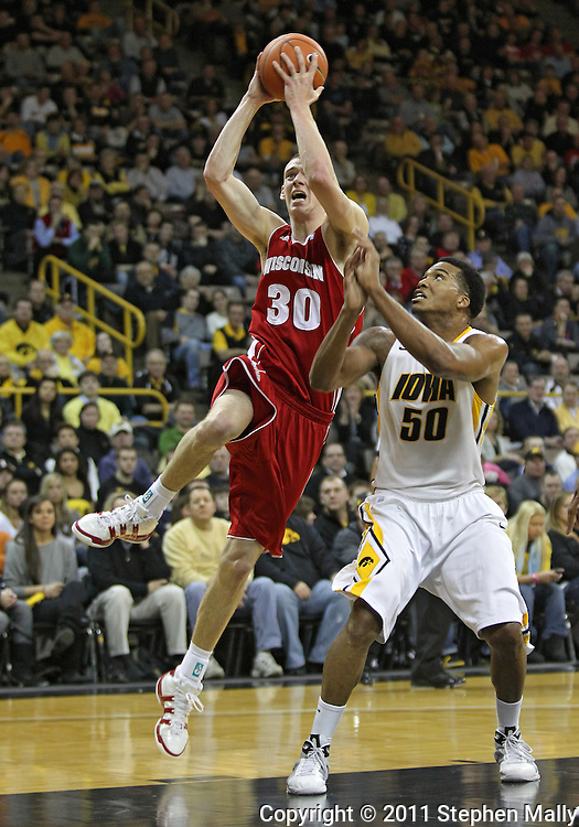 February 09 2011: Wisconsin Badgers forward Jon Leuer (30) puts up a shot as Iowa Hawkeyes forward Jarryd Cole (50) defends during the first half of an NCAA college basketball game at Carver-Hawkeye Arena in Iowa City, Iowa on February 9, 2011. Wisconsin defeated Iowa 62-59.