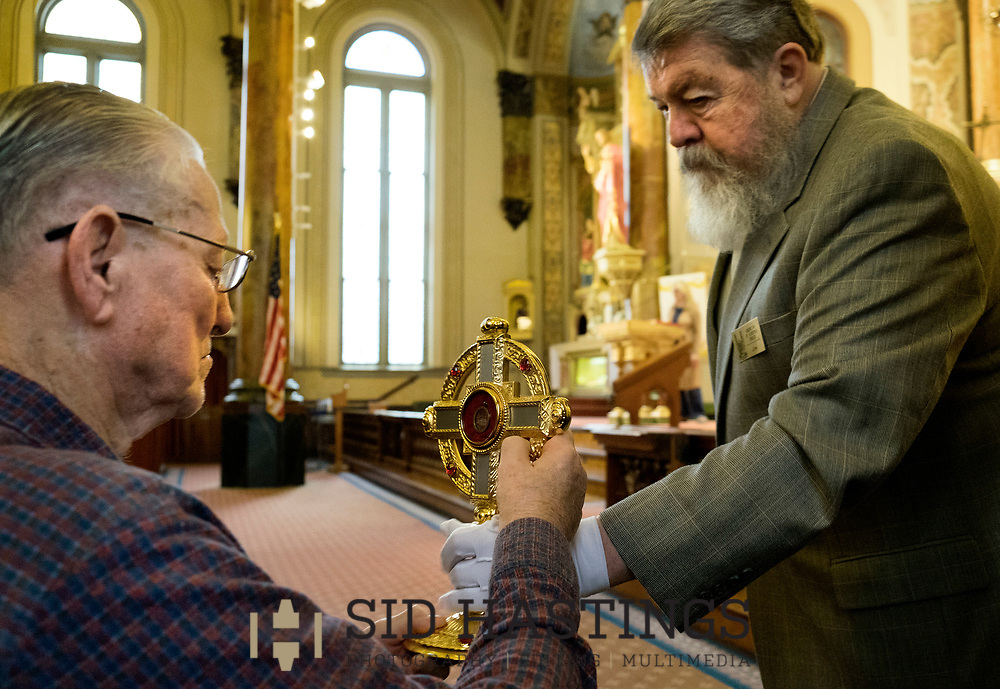 11 MARCH 2018 -- ST. LOUIS -- Francis Aubuchon (left), a descendant of German immigrant Ignatius Strecker, touches a relic of St. Peter Claver held by usher Jim Fuller during Mass at the Shrine of St. Joseph Sunday, March 11, 2018 in the Columbus Square neighborhood of St. Louis. Aubuchon and other Strecker descendants gathered to remember the healing of the Strecker, thought mortally ill, during an 1864 service honoring Jesuit priest Peter Claver, a missionary who worked among slaves in South America during the 17th century. Strecker's healing was among the miracles attributed to Claver that led to his 1888 canonization by Pope Leo XIII. Photo © copyright 2018 Sid Hastings.