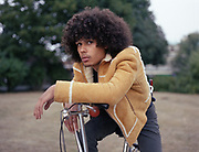 Young man leaning on handlebars of bike.