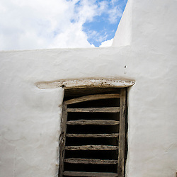 A typical white washed wall of Ibiza on a puffy white cloud day.