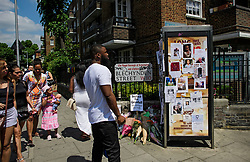 © Licensed to London News Pictures. 17/06/2017. London, UK.  Member of the public look at tributes and missing posters in front of  Grenfell tower block in west London following a devastating fire earlier this week. The blaze engulfed the 27-storey building killing 12 - with 34 people still in hospital, 18 of whom are in critical condition. The fire brigade say that they don't expect to find anyone else alive. Photo credit: Ben Cawthra/LNP