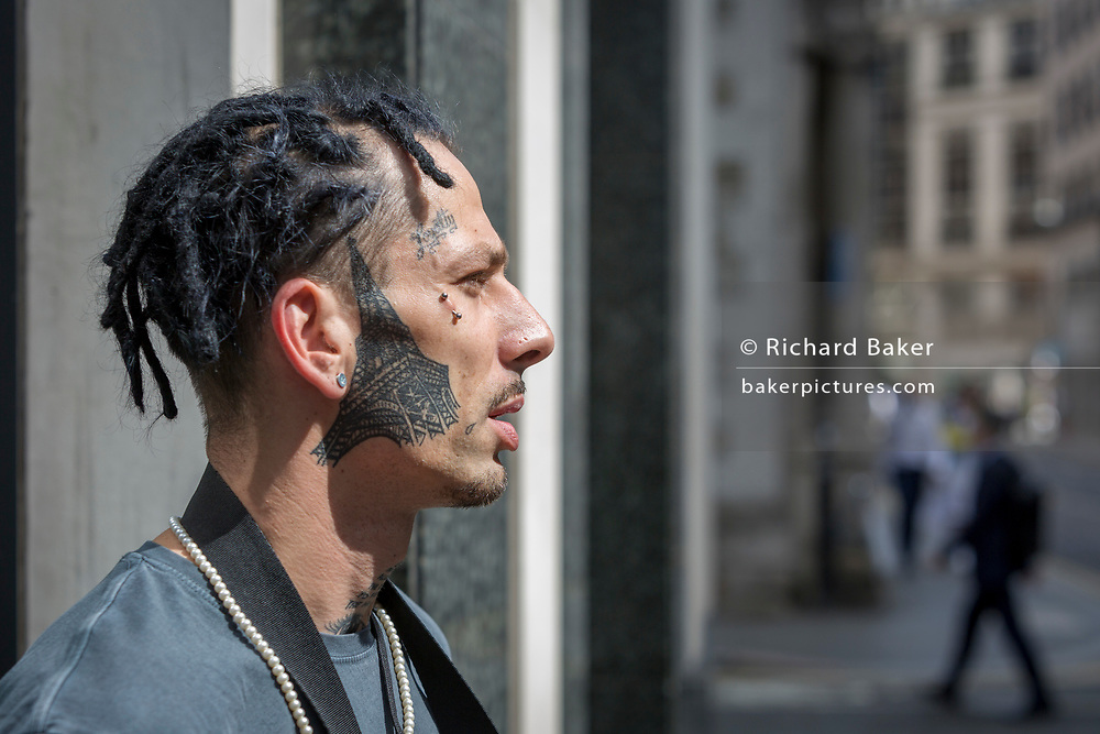 The musician known as Lil Fendi (Krzysztof Kmiecik) with the tattoo of the Eiffel Tower on his cheek and the word Loyalty above an eye, on 21st August 2018, in London, England.