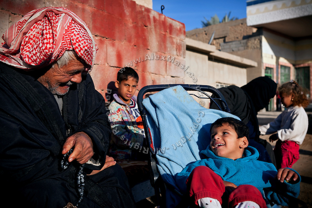 Jasim, 5, (right) one of Mohammed Thiab's two disabled young children, is sitting in his pram with his grandfather in the front-yard of their home in Fallujah, Iraq. The family has a healthy 8-year-old sister, Sauusan, born before the 2004 US-led battles, who regularly helps the parents in assisting her sick siblings. The parents and their relatives have no history of birth defects.