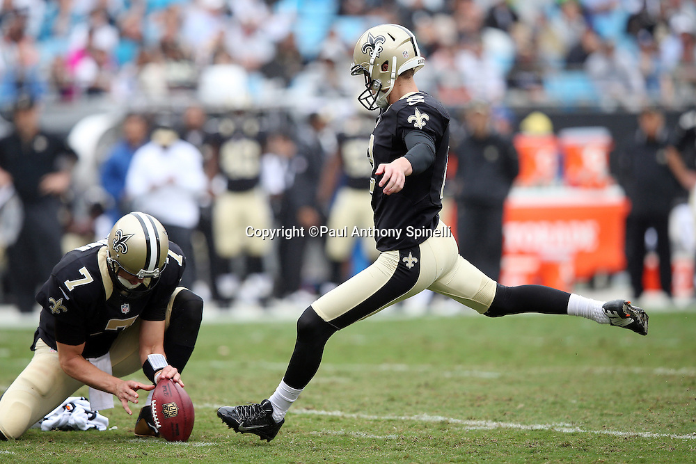 New Orleans Saints quarterback Luke McCown (7) holds while New Orleans Saints kicker Zach Hocker (2) kicks a second quarter extra point for a 10-0 Saints lead during the 2015 NFL week 3 regular season football game against the Carolina Panthers on Sunday, Sept. 27, 2015 in Charlotte, N.C. The Panthers won the game 27-22. (©Paul Anthony Spinelli)