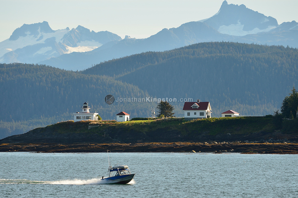A small motorboat cruises in front of Point Retreat Lighthouse, on the northern tip of Admiralty Island near Juneau, Alaska.