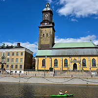 Landmarks along Norra Hamngatan in Gothenburg, Sweden <br /> This kayaker on the Great Harbor Canal is staring at the Christinae Kyrka clock tower. When finished in 1748, it was named in honor of Queen Christina. She was Sweden&rsquo;s queen from 1632 until 1654. The yellow building on the right is the German Church&rsquo;s sanctuary. The neighboring building on the left along Norra Hamngatan or North Harbour Street was built in 1753. The Sahlgrenska House was the private residence of Brigitta Sahlgren. She owned a huge sugary refinery and shipping business.