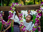 "17 MARCH 2018 - BANGKOK, THAILAND:  A girl pours floral water into an altar in Lumpini Park during a ""sticky rice merit making"" in the park in Bangkok. Sticky rice merit making is a merit making in the Isan / Lao style, when people present small amounts of cooked sticky rice (also known as glutinous rice) to Buddhist monks. Isan is the northeast region of Thailand.    PHOTO BY JACK KURTZ"