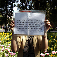 BEIJING, MAY 6: a woman shows a description of her daughter in a park, Beijing, May 6,2007. .Twice a week about 800 parents meet in the park trying to find suitable partners for their children. Similar activities are held throughout cities in China ..Due to heavy competition it's difficult for many young Chinese to find partners. This is true especially for women with high education levels like degrees from overseas  and PHDs.   Although customs are changing, there's a lot of pressure on young people to get married.     The children usually don't know of their parent's.activities...