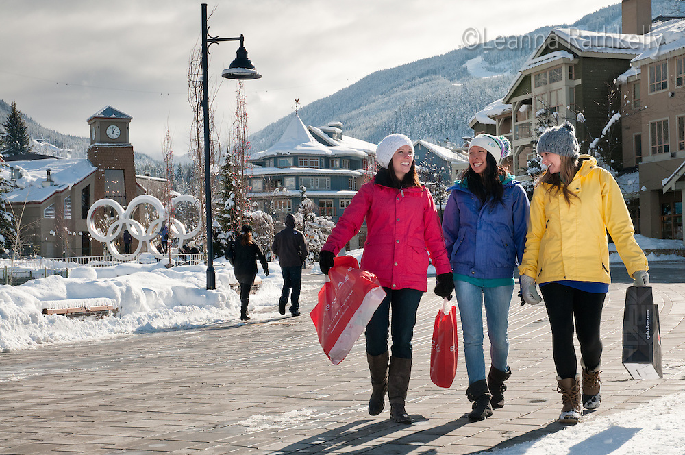 A trio of women shop Whistler Village on a winter day.