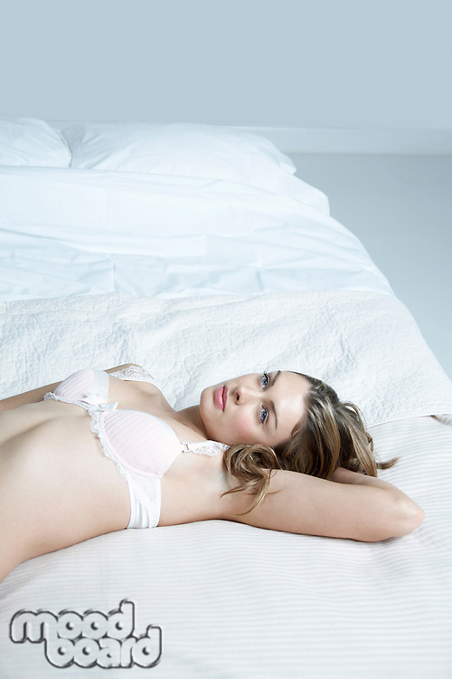Young woman in underwear lying on bed elevated view