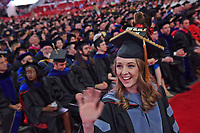 College of Veterinary Medicine graduate waves to family before crossing the stage to receive her diploma.
