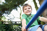 Young Boy sitting on monkey bars close up