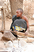 Datoga man prepares and lights the campfire using a goat skin bellows. Photographed in Africa, Tanzania, Lake Eyasi