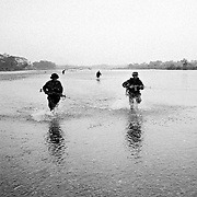 Government soldiers wade across a river in pursuit of escaping FARC rebels after a firefight. The FARC had been holding 40 civillians hostage at an illegal roadblock to entice the counter inurgency force to engage them.