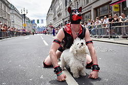 © Licensed to London News Pictures. 08/07/2017. London, UK. A man in a fetish dog costume is joined by a friendly pooch at the head of the parade.  Tens of thousands of visitors, many wearing eye-catching costumes, gather to watch and take part in the annual Pride in London Parade, the largest celebration of the LGBT+ community in the UK.   Photo credit : Stephen Chung/LNP