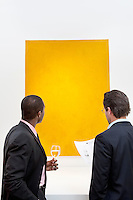 Two people looking at yellow painting on wall in museum