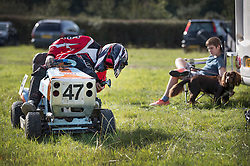 © Licensed to London News Pictures. 24/09/2016. Five Oaks, UK. A youth watches as his father gets ready to take part in a race at the Lawn Mower Racing World Championships. A weekend long set of races using specially adapted lawn mowers will see a World Champion announced on Sunday. Photo credit: Peter Macdiarmid/LNP