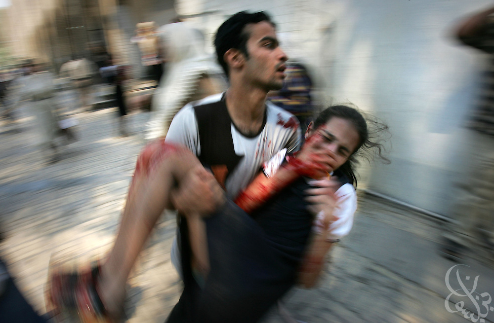 BAGHDAD, IRAQ - MAY 07, 2005:  An injured Iraqi schoolgirl is evacuated from the Aqida girls' school near the scene of a suicide car bombing in Tahrir square in Baghdad May 7, 2005. The bombing, which targeted a passing civilian contractor convoy just outside the school killed at least 6 persons, and wounded another 30 in the late morning explosion in the busy commercial area in the center of Baghdad.