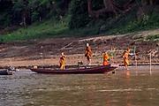 Laos, Luang Prabang Province. Buddhist monks at a Mekong river bank.