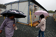 Women passing in front of the prefabricated houses that were build in Grinpia recreation center to house people from Taro village who lost their homes. Miyako, Iwate prefecture, Japan.