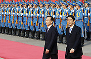 Chinese Premier Wen Jiabao (L)  walks with Japanese Prime Minister Shinzo Abe (R) past an honour guard at the Great Hall of the People in Beijing October 8, 2006. Abe, selected as prime minister two weeks ago, quickly arranged the visit to China aemphasize his desire to improve ties between the estranged Asian neighbors.