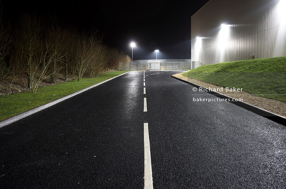 Seen from the middle of the road, an empty highway landscape is seen at night alongside a giant generic warehouse wall at the DIRFT warehouse logistics park in Daventry, Northamptonshire England. The tarmac is dark and the newly-painted white painted lines stand out. This 365 acre site off Junction 18 of the M1 motorway is a hub for road, rail and service infrastructure, some 2.3m sq.ft. of distribution and manufacturing floorspace had been constructed by 2004 and occupiers including Tesco?s, Tibbett & Britten plc, Ingram Micro, Royal Mail, the W.H. Malcolm Group, Eddie Stobart Ltd, Wincanton and Exel, have been attracted to this unique logistics location.