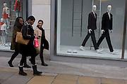 Three black girlfriends walk past odd mannequins in a central London street.