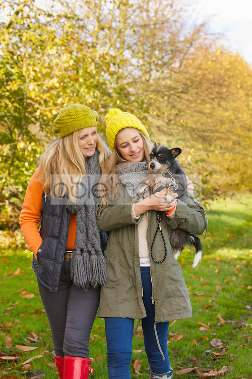 Mother and Daughter Walking in Park Carrying Dog