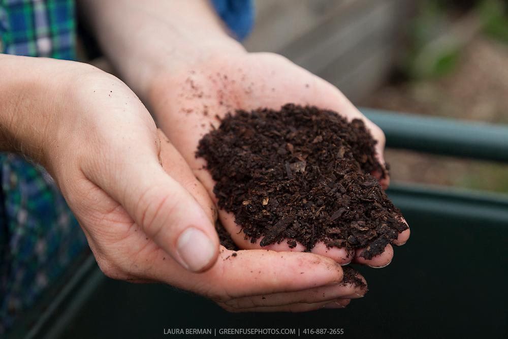 A handful of rich, dark, organic compost against a blue plaid shirt.
