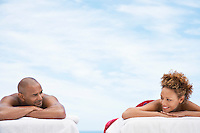 Couple lying on massage tables outside head and shoulders