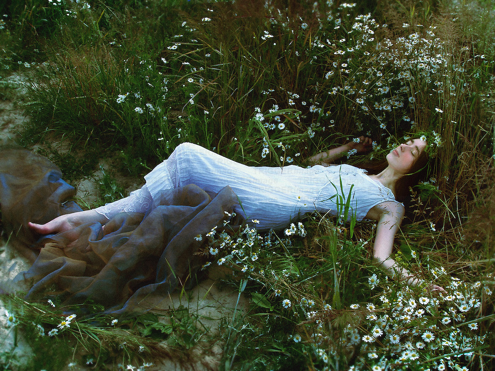 A woman laying on a meadow full of camomile flowers, dressed in a white gown, posing in a lazy sleepy manner.