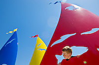 "Casey Barrett, 5, pokes his head out of one of the fish cutouts of the new public art display ""Catch the Wind"" which was dedicated Monday at its installation site along Northwest Boulevard and Seltice Way."